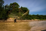 Fisherman throwing fishnet high into the air