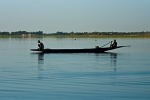 A man and a kid working in the late afternoon on their pirogue on the Niger river near ferry crossing to Timbuktu, Mali. Photo by Marko Preslenkov.