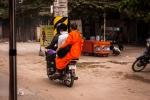 Buddhist monk sitting sideways on a speeding scooter