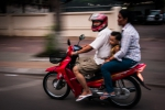 Family of three on a red Suzuki scooter