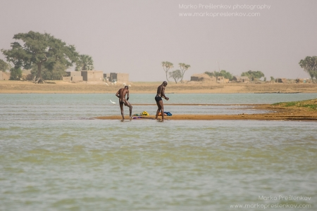 Two men washing on the banks of Niger river