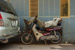 Sleeping on his Honda Dream motorbike in Hanoi