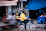 Yellow hoodie cycling past food stall