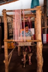 Lao woman weaving on traditional wooden loom