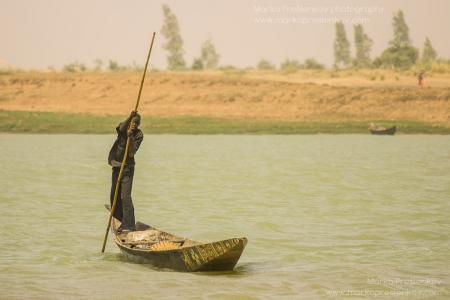 Boy using a pole to push pinasse across the river