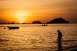 Sunset behind a swimmer on Bounty Beach