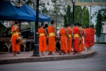 Monks rounding the street corner at alms procession